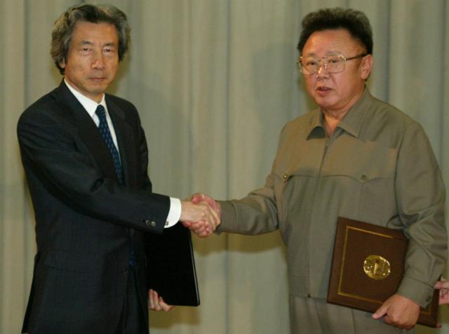 2002年9月17日、平壌で初の日朝首脳会談を終え、お互いに署名した日朝平壌宣言を交換、握手する小泉純一郎首相と金正日総書記=百花園迎賓館