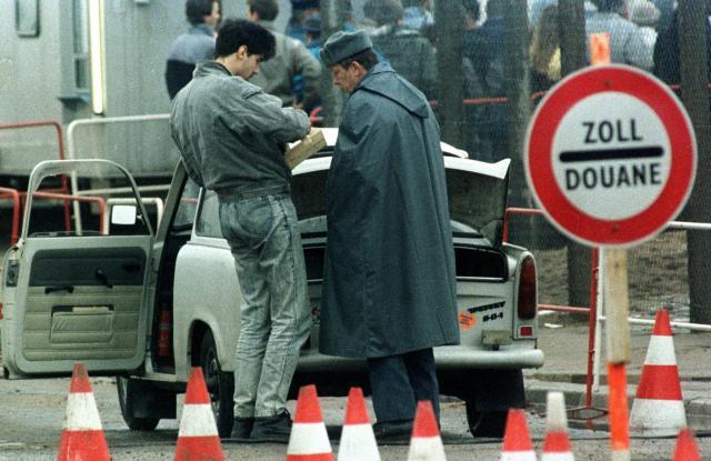 ベルリン中心部にあるポツダム広場の検問所で、東ドイツの警官に荷物の検査をされる市民=1989年11月24日