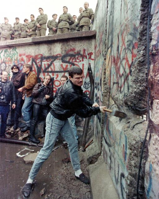 東ベルリンの国境警備隊が見下ろすなか、ベルリンの壁を壊す市民=1989年11月11日