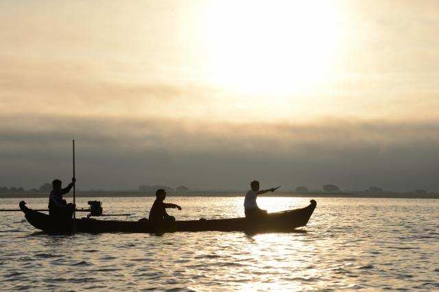 朝焼けの中、舟を出す漁師。とれるのは主に小魚だといいます=2017年12月、ミャンマー中部
