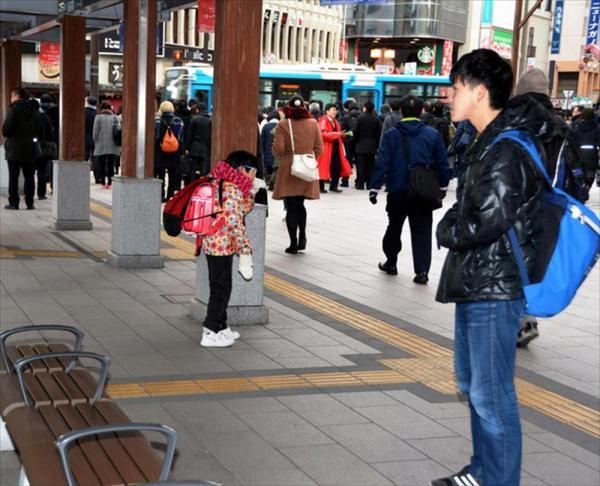 乗り継ぎのバスを待つ陽向子さん(手前左)。見守り役の中江光貴さん(手前右)は、他人のふりをしている=長野市