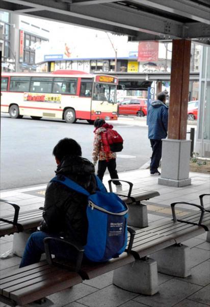 乗り継ぎのバスが来ないか、心配そうに見つめる陽向子さん(中央)。中江光貴さん(手前)が見守っている=長野市