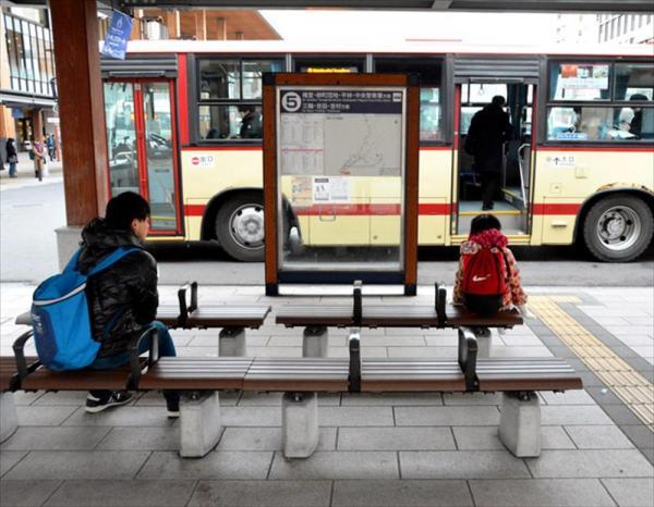 乗り継ぎのバスを待つ陽向子さん。行き先の違うバスが来ても乗らないように気を付ける。左は見守り役の中江光貴さん=長野市