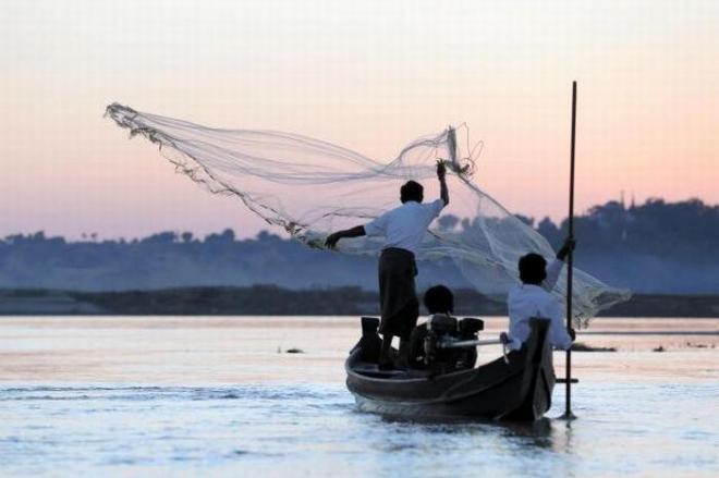 夕焼けの中、川に網を投げるマウンレイさん。「昔はもっとたくさんの魚がとれたんだが……」と少し寂しそう=2017年12月、ミャンマー中部、杉本康弘撮影