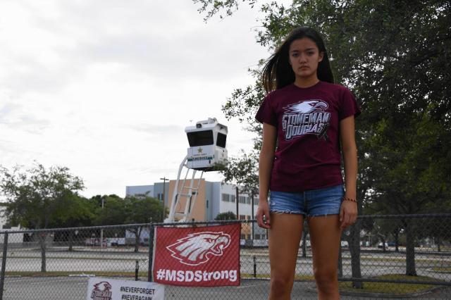 マージョリー・ストーンマン・ダグラス高校の前に立つエンゲルバート美愛さん。事件後、警察の監視塔が設置されるなど校内は厳重な警備が敷かれている=2018年3月31日