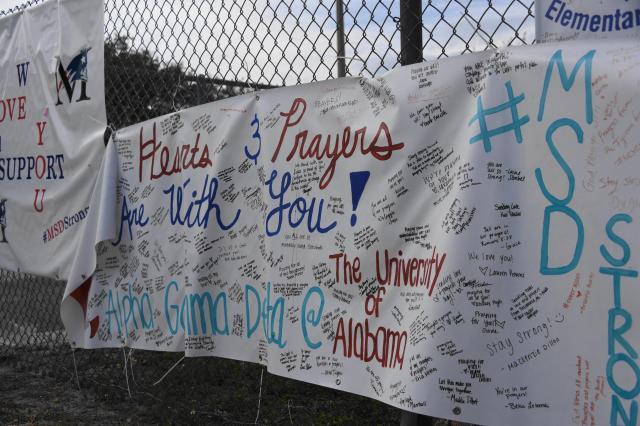 マージョリー・ストーンマン・ダグラス高校のフェンスには生徒らへの応援メッセージが掲げられていた=2018年3月31日