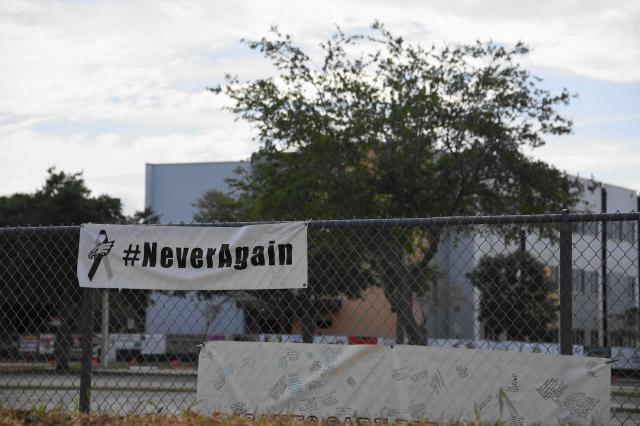 「Never Again」と再発防止の訴えがフェンスに掲げられていた。後ろの校舎で事件が起きた=2018年3月31日
