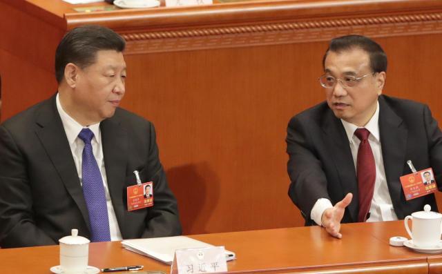 全人代で、習近平国家主席(左)に言葉をかける李克強首相=2018年3月18日、杉本康弘撮影