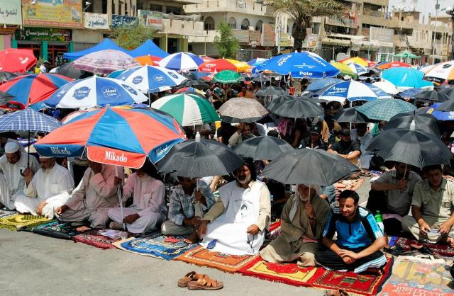 バグダッド東部のサドルシティー。日中に直射日光を浴びると、命の危険すら感じるほど暑い。それでもイスラム教の集団礼拝がある金曜日には、モスク周辺に多くの人が集まる。欠かせないのが日傘。大型霧吹きのようなもので水をかけて回るサービスも登場する