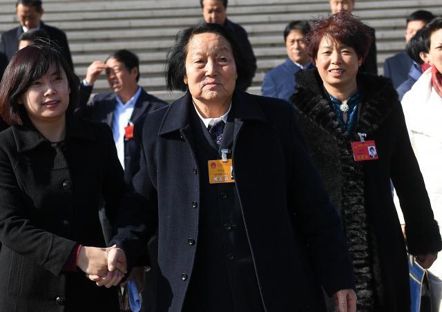 全人代で一度も反対票を投じたことがなく、ネット上で「生きた化石」と呼ばれている88歳の申紀蘭さん(中央)。今年も代表に選ばれた=2018年1月、中国・山西省