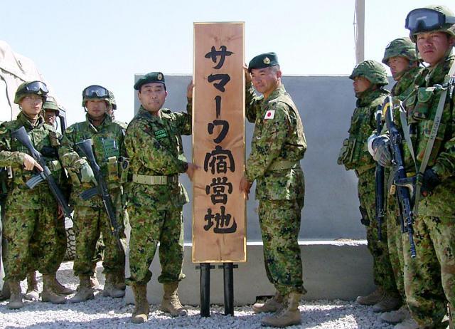 2004年4月2日、イラク・サマワの宿営地に看板を掲げる先崎一・陸上幕僚長と、番匠幸一郎・第1次復興支援群長