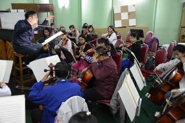 練習中、山本さんは英語やミャンマー語で「私を見て」と何度も繰り返した。「指揮者と呼吸を合わせることが、演奏の技術よりも大切」という=2018年1月、ヤンゴン