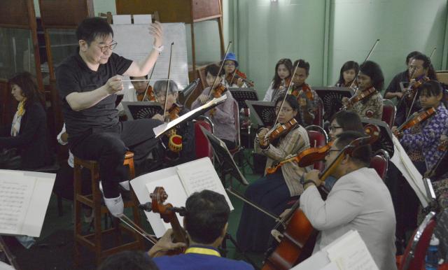 練習では、通訳がつくこともあるが、いないときもある。山本さんは英語を何度も繰り返して指示を楽団員に伝えていた=2017年6月、ヤンゴン