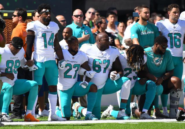 アメリカンフットボールプロリーグNFLの試合前、国歌斉唱中にひざをついて人種差別に抗議するマイアミ・ドルフィンズの選手=2017年9月