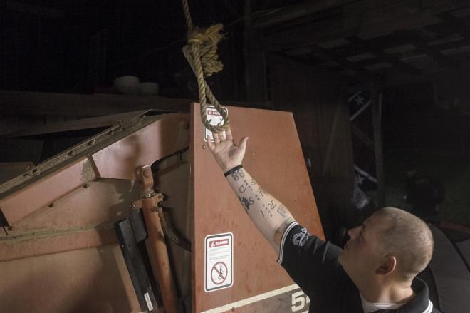 アメリカ・テネシー州の農家のはりにぶら下げられた縛り首の縄を見せる白人至上主義団体の男性=2015年7月