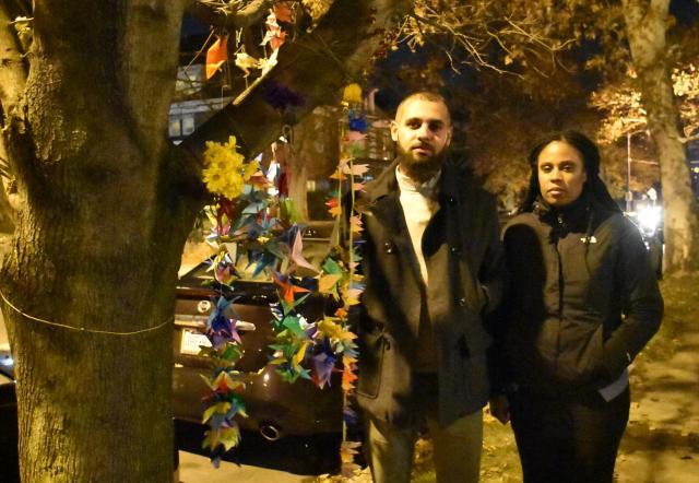 縛り首の輪が見つかった街路樹の脇に立つギブソンさん(左)とモーガンさん。事件を聞き、連帯を示そうと近所の住民や子どもたちが結びつけた折り紙や飾りがあった=昨年11月、ピッツバーグ、香取啓介撮影