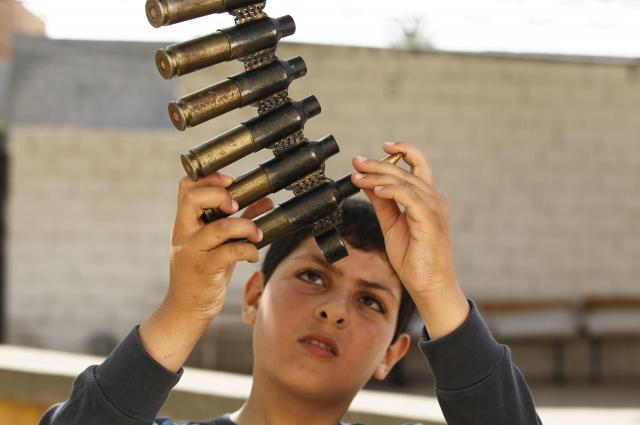 リビアの学校で、銃弾を点検する子ども=2011年5月、ロイター