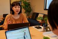 同僚と話す里田恵梨子さん。社内には子育てをしながら働く女性が多い
