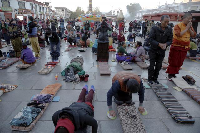 ラサで五体投地とよばれる祈りをささげるチベットの人々=2015年11月20日