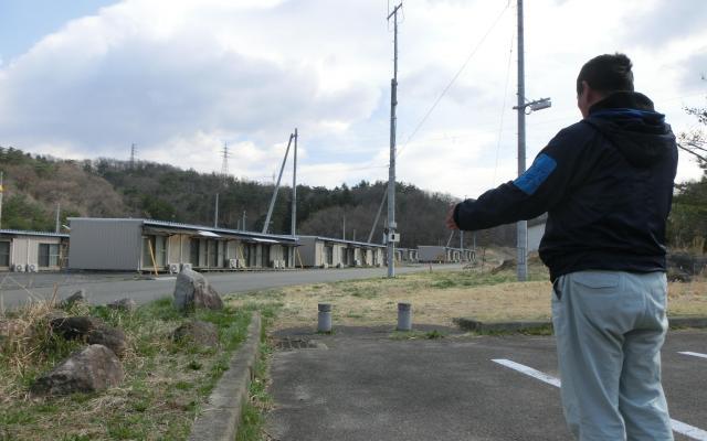 リヤカーハウスを一時置いていた本宮市の運動公園駐車場を示す川上哲治さん。奥は閉鎖された高木応急仮設住宅