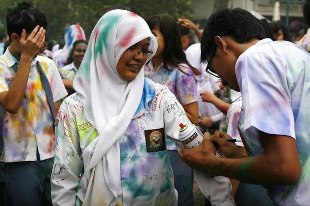 制服に落書きをするインドネシアの卒業生たち