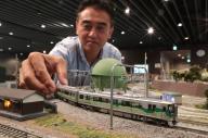 愛知環状鉄道2000系と、鉄道模型メーカー「カトー」の川崎太志さん=東京都新宿区、吉本美奈子撮影