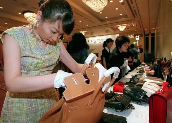 ブランドオークションで出品されるエルメスのバッグをチェックする中村うさぎさん=1999年6月6日