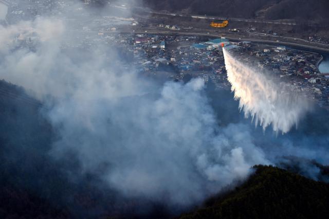 消火活動にあたる自衛隊のヘリコプター=2015年3月31日、岡谷市、朝日新聞ヘリから、日吉健吾撮影