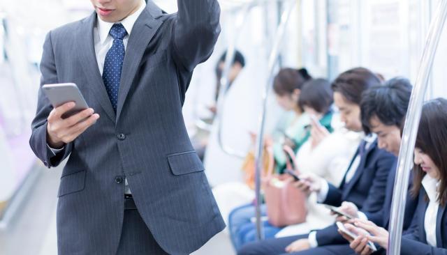電車通勤の空き時間を利用して副業のメール処理を行う人も(写真はイメージ)