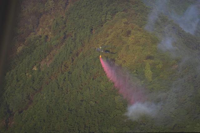 くすぶり続ける山林に消火剤を散布する自衛隊のヘリ=1994年8月17日、長野県更級郡上山田町で(長野朝日放送ヘリから) ※画像と記事は関係ありません