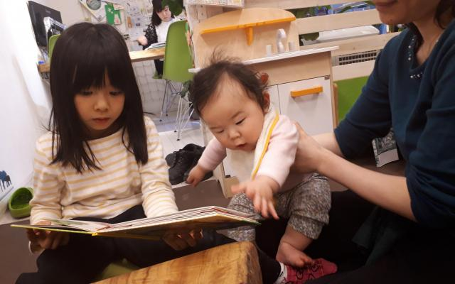 不動産事務所は週1回、親子連れの集いの場として開放する。遊びに来た赤ちゃんに本を読んであげる長女・美波ちゃん(5)。「成長の瞬間を見逃さないのも醍醐味です」と直樹さん