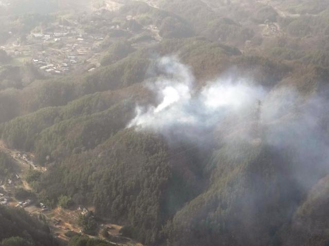 燃えて白い煙を上げる山林=2018年4月2日、飯田市千代、長野県警提供