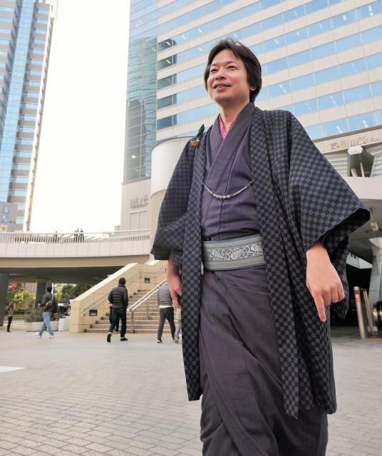 着物姿で高層ビルに囲まれる田中達彦さん