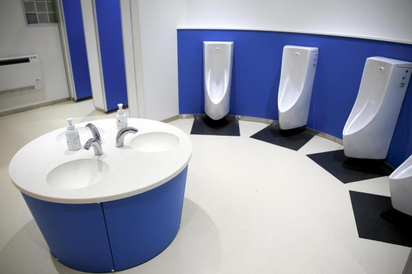 小学校のトイレ。小便器が曲線状に並べられ、人目が気にならない=山梨県北杜市