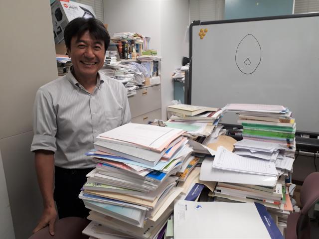 積み上げられた資料を前にほほえむ戸梶亜紀彦教授=東京都文京区の東洋大学白山キャンパス