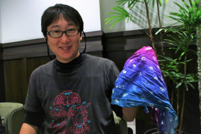 お気に入りの虫柄手ぬぐいを手に笑う平井さん。Tシャツにはハエトリグモのイラスト。