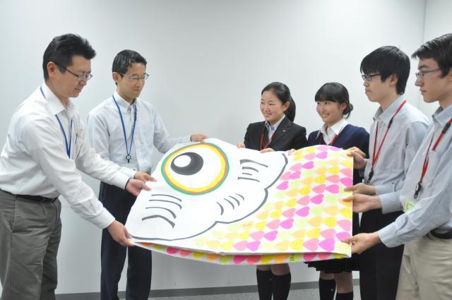 防衛省の職員に、集まったこいのぼり型の署名を手渡す「がっこいっしょ隊」のメンバーら=2018年5月、東京都新宿区、軽部理人撮影