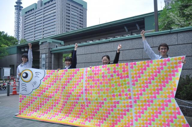 集まった署名を防衛省の前で広げる「がっこいっしょ隊」のメンバーら=2018年5月、東京都新宿区、軽部理人撮影