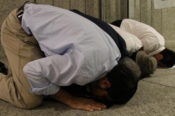 地面にひれ伏して祈る新月観測会のメンバーたち