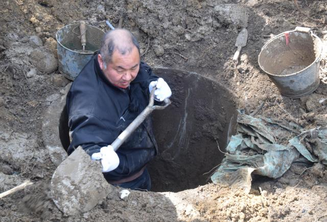 コンクリート管の中に入ってつぼを探す参加者=4月8日、三重県伊賀市上野愛宕町