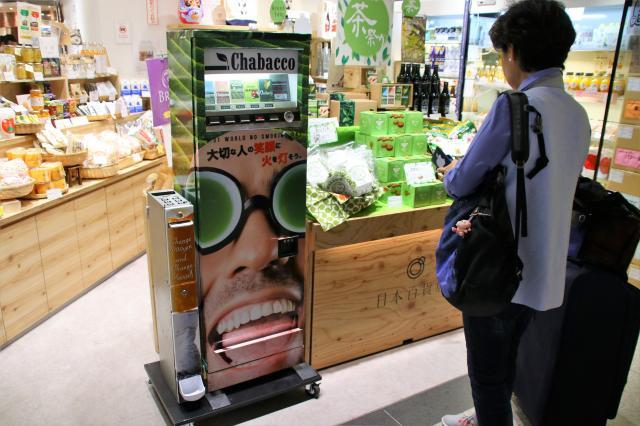 期間限定で売店に設置された自動販売機を眺める女性。