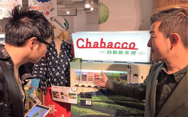 Chabaccoの自販機前で接客する森川翔太さん(右)。