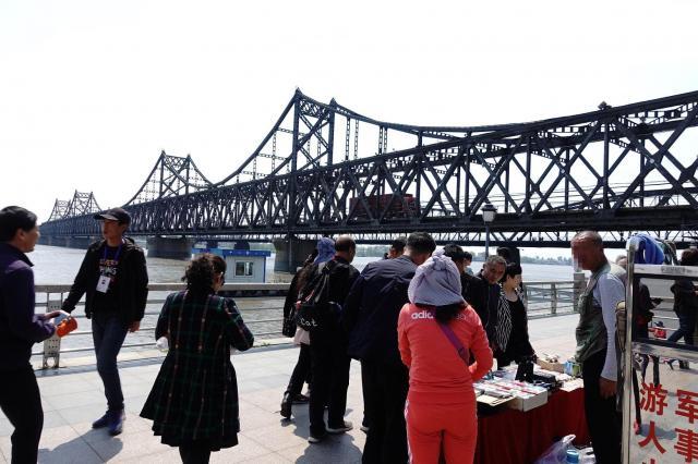 丹東と対岸の北朝鮮を結ぶ橋の周辺では、多くの露天商が北朝鮮製のタバコや紙幣を土産物として販売している。カメラを向けると「写真を撮らないで」と注意された。(画像の一部に処理を施してあります)