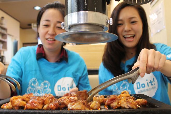 鶏肉を焼く「Do it! 松阪鶏焼き肉隊」メンバーたち=三重県松阪市
