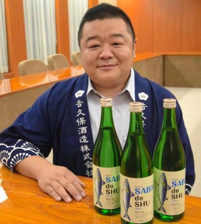 サバ専用の日本酒「サバデシュ」と、吉久保酒造の吉久保博之社長=水戸市