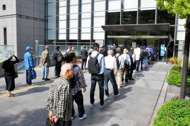 平日でも約50人が行列をつくって開館を待つ。夏休みには学生が加わり、さらに長い列になる=2018年4月26日午前、大阪市西区の市立中央図書館、半田尚子撮影