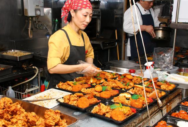 厨房で弁当箱に具を詰める女性店員。