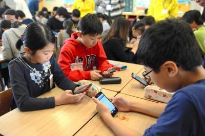 教育用アプリを入れた実際のスマートフォンで、ネットのトラブルを疑似体験する児童たち=2017年10月24日、名古屋市中村区