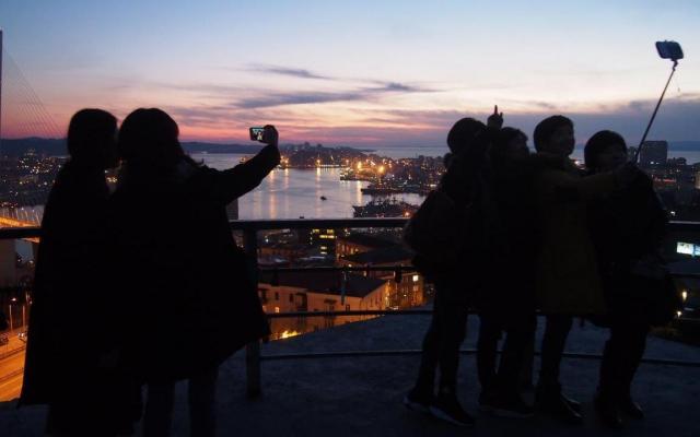 ウラジオストク市内を一望する観光名所「鷹の巣展望台」で自撮りする観光客