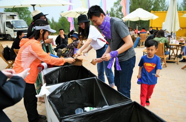 大人も子供も分別に精が出ます=2018年5月19日、中国・河北省懐来県、冨名腰隆撮影